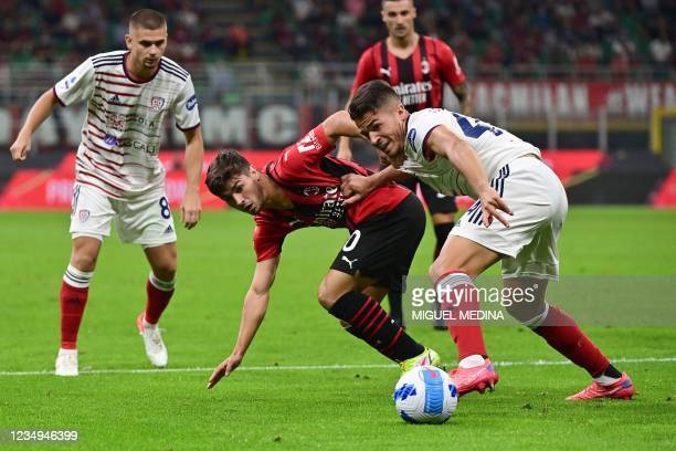 Milan's Spanish midfielder Brahim Diaz challenges Cagliari's Italian defender Andrea Carboni during the Italian Serie A football match between AC...