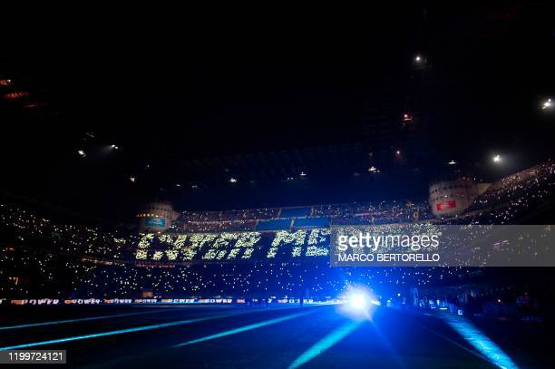 AC Milan's supporters hold lights to write Inter Shit during the Italian Serie A football match Inter Milan vs AC Milan on February 9 at the San Siro...