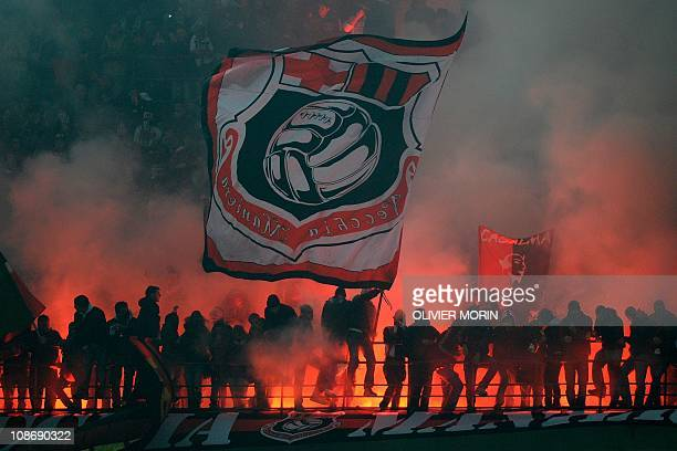 AC Milan's supporters wave flags and alight flares during their team's Italian Serie A football match against Inter Milan on November 14 2010 in San...