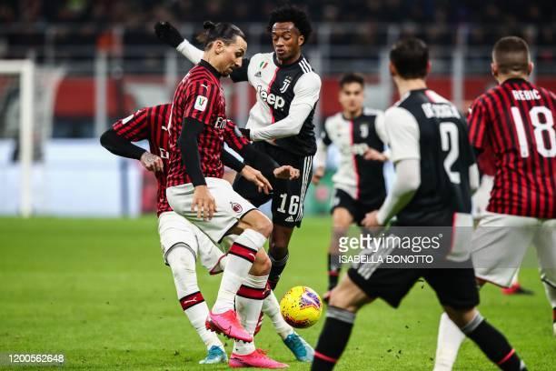 Milan's Swedish forward Zlatan Ibrahimovic challenges Juventus' Colombian midfielder Juan Cuadrado during the Italian Cup semi-final first leg...