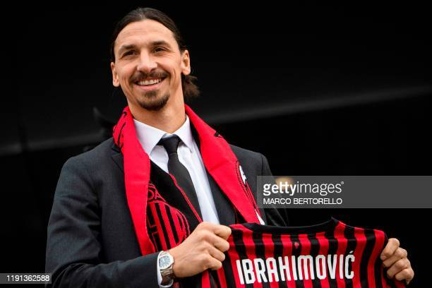 TOPSHOT Milan's Swedish forward Zlatan Ibrahimovic poses with his new jersey during his official presentation as new AC Milan player at the club's...