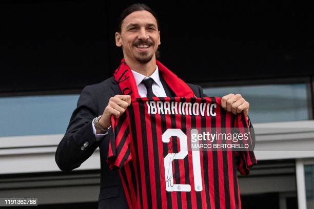 Milan's Swedish forward Zlatan Ibrahimovic poses with his new jersey during his official presentation as new AC Milan player at the club's...