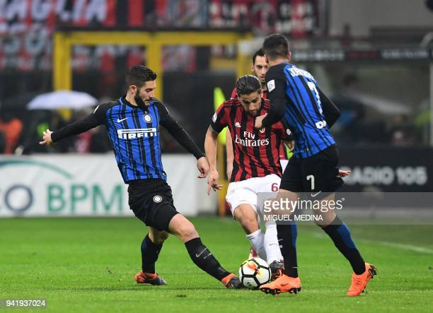 AC Milan's Swiss defender Ricardo Rodriguez vies with Inter Milan's Italian midfielder Roberto Gagliardini and Inter Milan's Portuguese forward Joao...