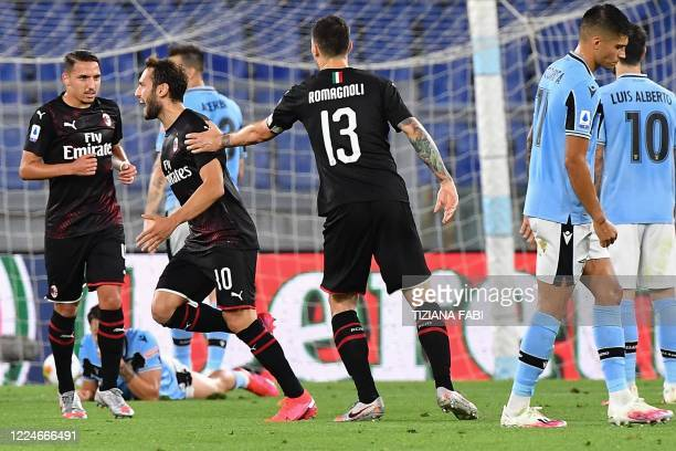 Milan's Turkish forward Hakan Calhanoglu celebrates after opening the scoring during the Italian Serie A football match Lazio vs AC Milan played...
