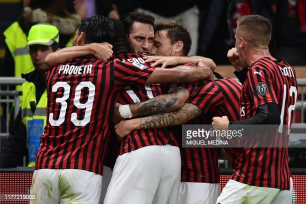 AC Milan's Turkish forward Hakan Calhanoglu celebrates with teammates after opening the scoring during the Italian Serie A football match AC Milan vs...