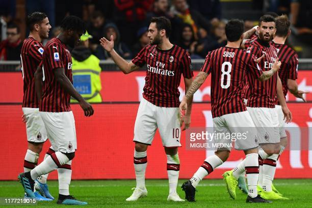 Milan's Turkish forward Hakan Calhanoglu celebrates with teammates after opening the scoring during the Italian Serie A football match AC Milan vs...