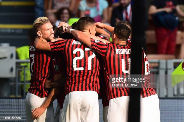 AC Milan's Turkish forward Hakan Calhanoglu is congratulated by his teammates after scoring during the Italian Serie A football match between AC...