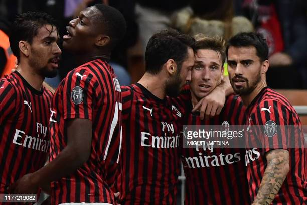 Milan's Turkish forward Hakan Calhanoglu kisses AC Milan's Argentinian midfielder Lucas Biglia as he celebrates with teammates after opening the...