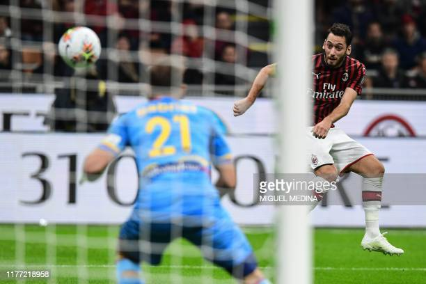 Milan's Turkish forward Hakan Calhanoglu shoots to open the scoring past Lecce's Brazilian goalkeeper Gabriel during the Italian Serie A football...