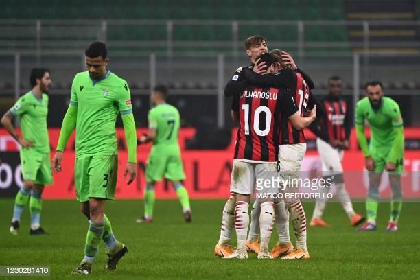 Milan's Turkish midfielder Hakan Calhanoglu , AC Milan's Italian forward Daniel Maldini and AC Milan's Norwegian forward Jens Petter Hauge embrace at...