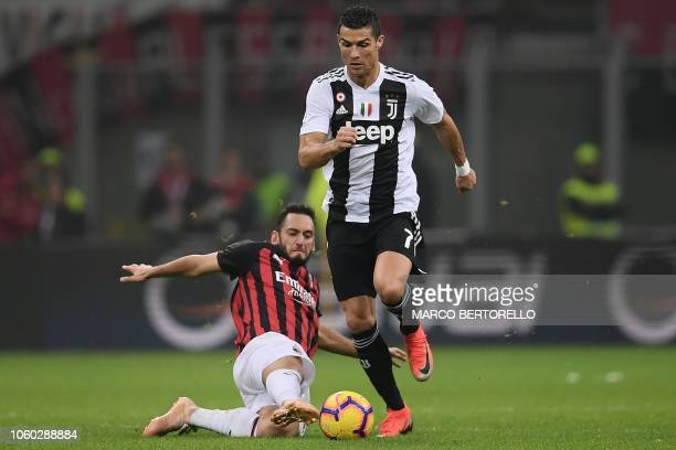 AC Milan's Turkish midfielder Hakan Calhanoglu attempts to tackles Juventus' Portuguese forward Cristiano Ronaldo during the Italian Serie A football...