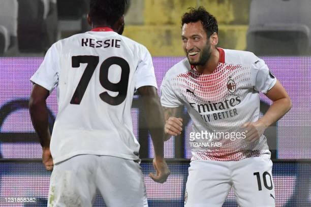 Milan's Turkish midfielder Hakan Calhanoglu celebrates after scoring his team's third goal during the Italian Serie A football match Fiorentina vs AC...