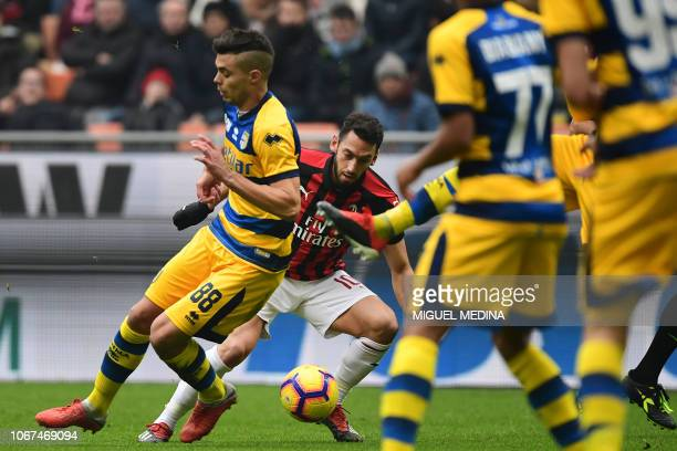 AC Milan's Turkish midfielder Hakan Calhanoglu fights for the ball with Parma's Italian midfielder Alberto Grassi during the Italian Serie A football...