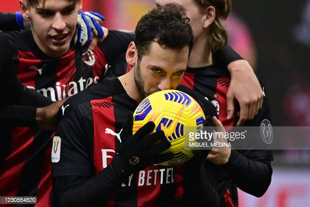 Milan's Turkish midfielder Hakan Calhanoglu kisses the ball after he scored the winning penalty in the penalty shootout during the Italian Cup round...