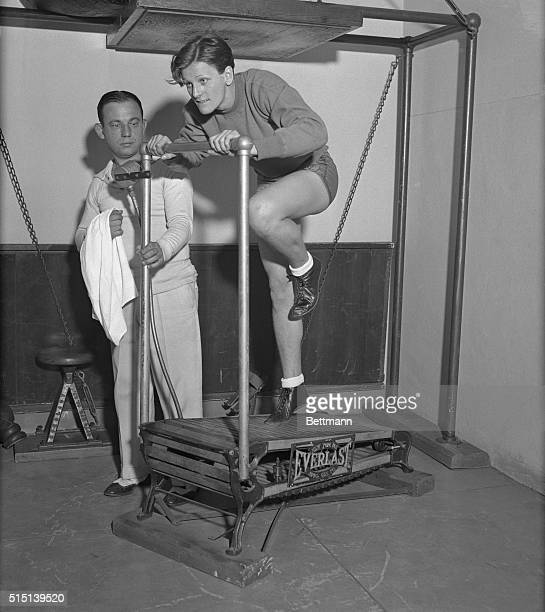 Mildred 'Babe' Didrickson the sensational girl athlete of Beaumont Texas loosens up the kinks here in her legs on a running machine in Artie...