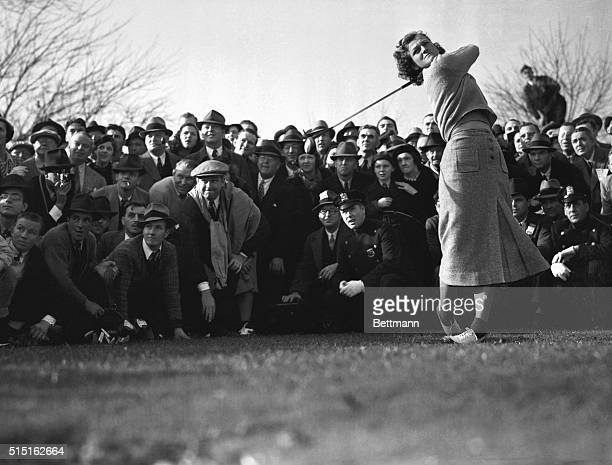 "Mildred ""Babe"" Didrikson, golf star from Texas, driving off, as the gallery hems her in, in the four-ball charity golf match at Fresh Meadow Country..."