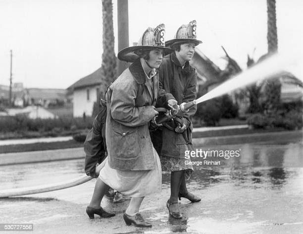 Mildred E Carroll and Bobby Wells demonstrate their firefighting abilities in dresses and heels They took classes at the local fire department in...