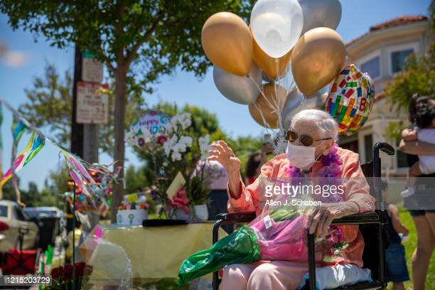 Mildred ``Millie'' Stratton waves to a caravan of cars led by the Alhambra Police and Fire parading past her home celebrating her 102nd birthday on...