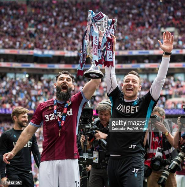 Mile Jedinak and assistant manager John Terry of Aston Villa celebrate with the trophy after the Sky Bet Championship Play-off Final match between...