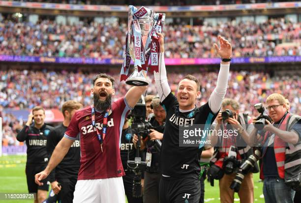 Mile Jedinak of Aston Villa lifts the trophy with John Terry Assistant Head Coach of Aston Villa the Sky Bet Championship Playoff Final match between...