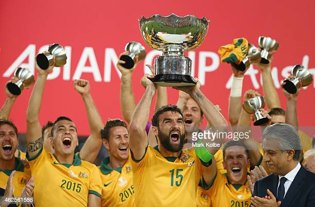 Mile Jedinak of Australia and his team celebrate as he lifts the trophy after victory during the 2015 Asian Cup final match between Korea Republic...