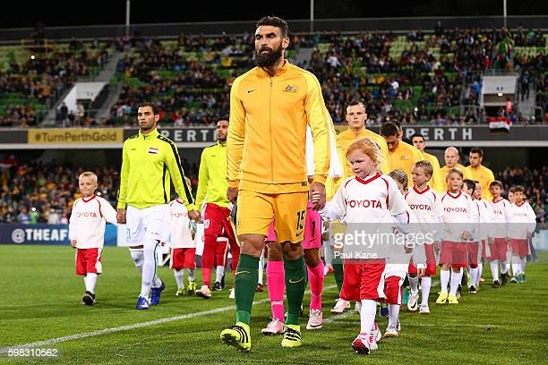 Mile Jedinak of Australia and Saad Abdulameer of Iraq lead their teams out onto the field during the 2018 FIFA World Cup Qualifier match between the...