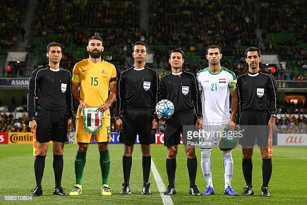 Mile Jedinak of Australia and Saad Abdulameer of Iraq pose with match officials after the coin toss during the 2018 FIFA World Cup Qualifier match...