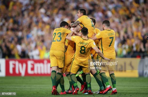 Mile Jedinak of Australia celebrates with team mates after scoring the first goal as Tim Cahill of Australia jumps over the top during the 2018 FIFA...