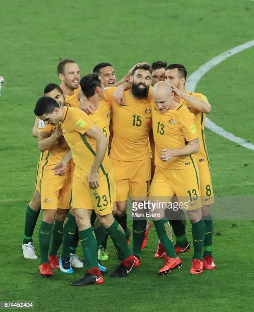 Mile Jedinak of Australia is mobbed by team mates after scoring a goal during the 2018 FIFA World Cup Qualifiers Leg 2 match between the Australian...