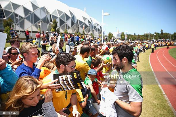 Mile Jedinak of Australia signs autographs after an Australian Socceroos training session at Collingwood training Ground on January 4, 2015 in...