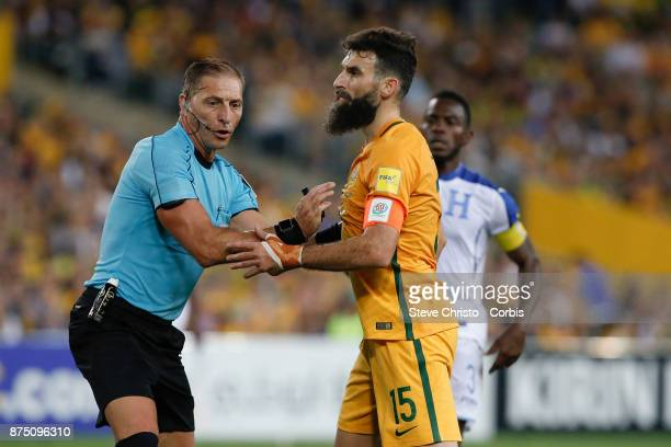 Mile Jedinak of the Australia is held back by referee Nestor Fabian Pitana during the 2nd leg of the 2018 FIFA World Cup Qualifier between the...