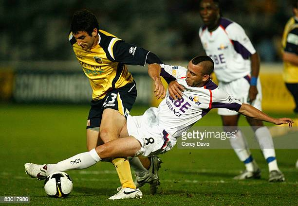 Mile Jedinak of the Mariners is tackled by James Robinson of the Glory during the round six A-League match between the Central Coast Marinersand the...