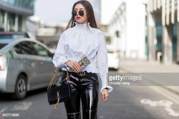 Milena Karl wearing black cropped vinyl pants white blouse YSL bag Valentino heels outside Julien Macdonald on day 2 of the London Fashion Week...