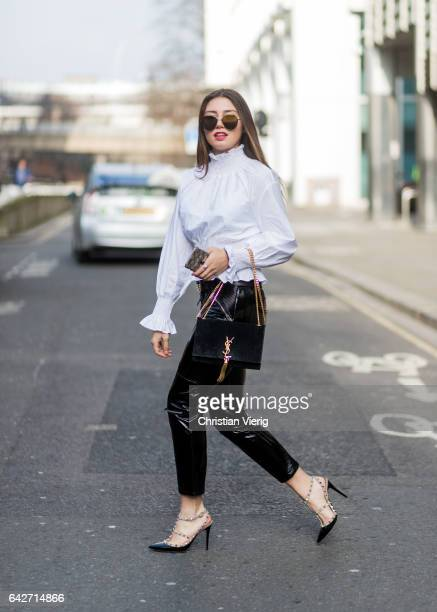 Milena Karl wearing black cropped vinyl pants white blouse YSL bag Valentino heels outside Julien Macdonald on day 2 of the London Fashion Week...