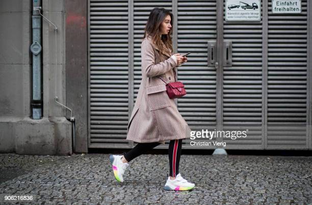 Milena Karl wearing checked coat red Chanel bag sneakers leggings is seen outside Lana Mueller during the Berlin Fashion Week January 2018 on January...