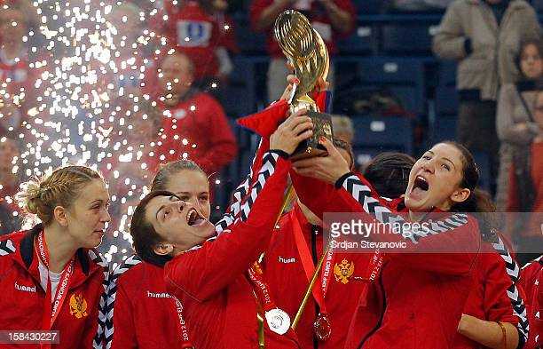 Milena Knezevic and Ana Dokic of Montenegro lift the trophy during the Women's European Handball Championship 2012 medal ceremony at Arena Hall on...