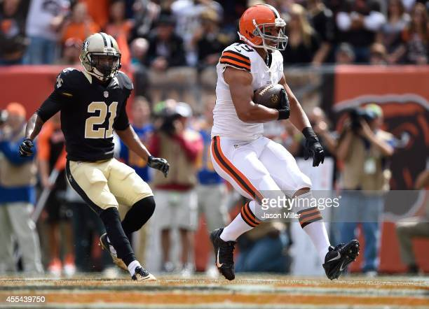 Miles Austin of the Cleveland Browns scores a touchdown in front of Patrick Robinson of the New Orleans Saints during the first quarter at...