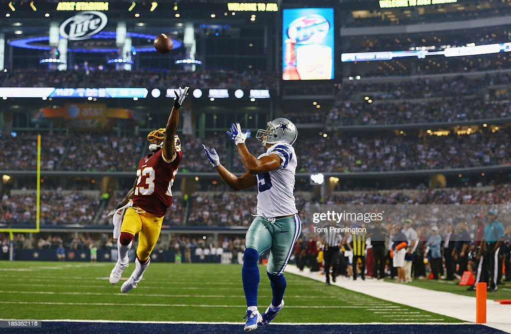 Miles Austin #19 of the Dallas Cowboys tries to catch a pass in the end zone against DeAngelo Hall #23 of the Washington Redskins at AT&T Stadium on October 13, 2013 in Arlington, Texas.