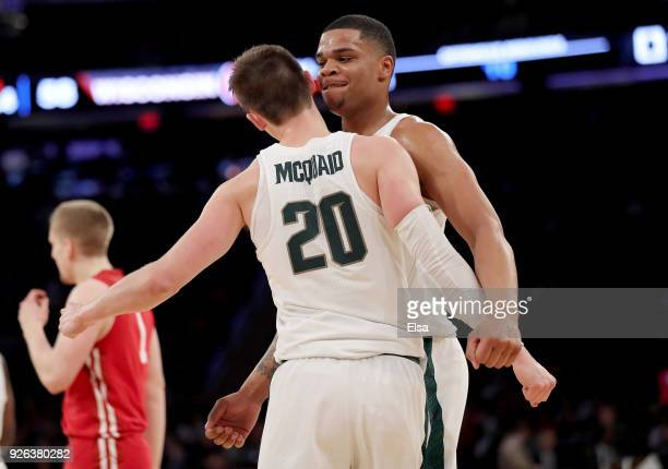 Miles Bridges congratulates teammate Matt McQuaid of the Michigan State Spartans after a shot in the second half against the Wisconsin Badgers during...