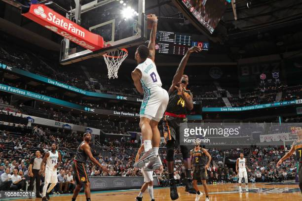 Miles Bridges of the Charlotte Hornets dunks the ball while guarded by Dewayne Dedmon of the Atlanta Hawks on November 6 2018 at Spectrum Center in...