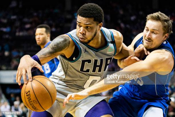 Miles Bridges of the Charlotte Hornets is guarded by Ryan Broekhoff of the Dallas Mavericks during the fourth quarter during their game at Spectrum...