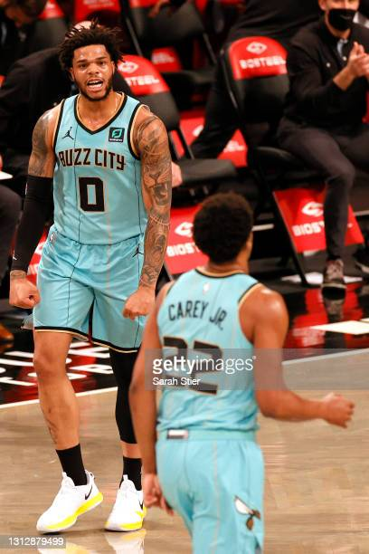 Miles Bridges of the Charlotte Hornets reacts with Vernon Carey Jr. #22 after scoring during the first half against the Brooklyn Nets at Barclays...
