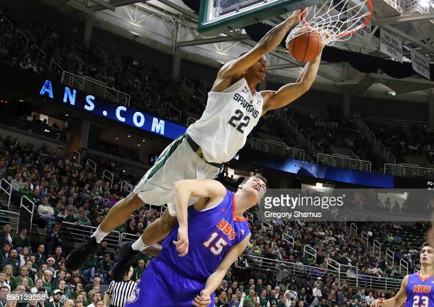 Miles Bridges of the Michigan State Spartans dunks over Edward Hardt of the Houston Baptist Huskies during the first half at the Jack T Breslin...
