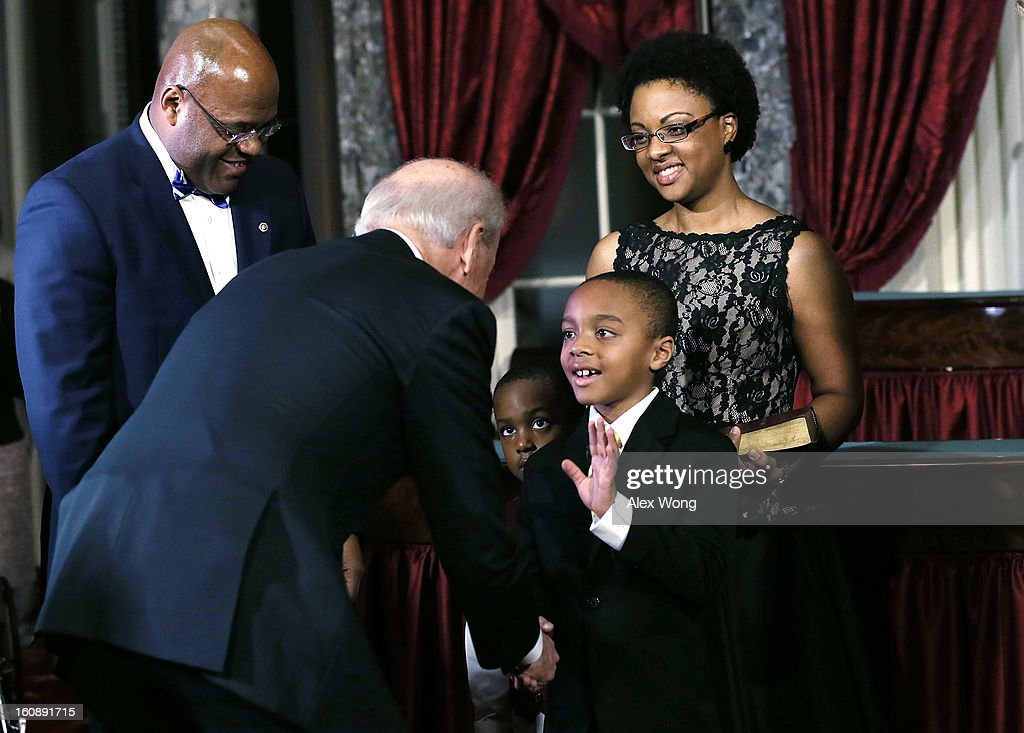 Miles Cowan (4th L), son of U.S. Sen. William 'Mo' Cowan (D-MA) (L), greets U.S. Vice President Joseph Biden (2nd L) as his mother Stacy (R), and brother Grant (3rd L) look on during his father's re-enacted swearing-in February 7, 2013 at the Old Senate Chamber of the U.S. Capitol in Washington, DC. Cowan was appointed by Massachusetts Governor Deval Patrick as interim U.S. Senator to fill the seat that left vacant by Secretary of State and former Senator John Kerry.