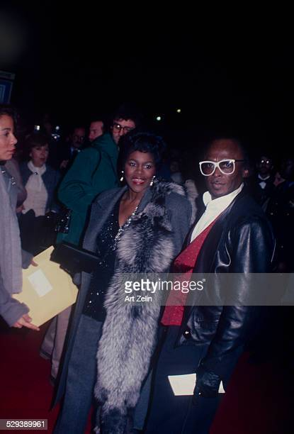 Miles Davis with his girlfriend Cicely Tyson He is wearing a leather jacket and white glases she has a fur circa 1970 New York