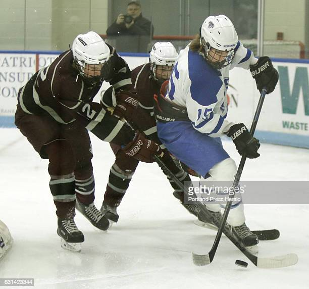 Miles Eaton of Kennebunk looks to move the puck away from Ryan Megathlin left and Andy Moore of Greely during a game at the Harold Alfond Forum at...