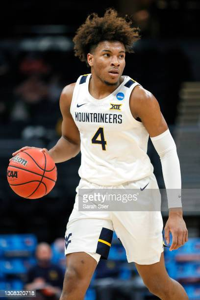 Miles McBride of the West Virginia Mountaineers controls the ball against the Syracuse Orange in the first half of their second round game of the...