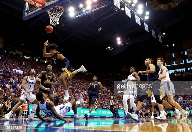 Miles McBride of the West Virginia Mountaineers crashes into Ochai Agbaji of the Kansas Jayhawks as he drives on a fast break during the game at...