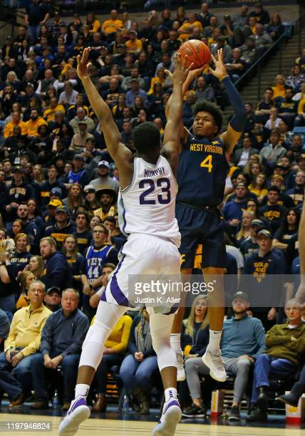 Miles McBride of the West Virginia Mountaineers pulls up for a three against Montavious Murphy of the Kansas State Wildcats at the WVU Coliseum on...