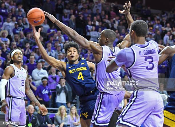 Miles McBride of the West Virginia Mountaineers puts up a shot around Makol Mawien of the Kansas State Wildcats during the first half at Bramlage...